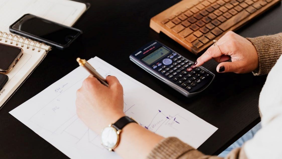 A bookkeeper performing a calculation and taking notes